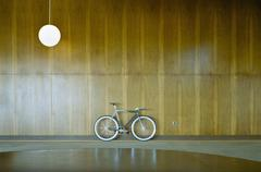 Bike parked against wood paneling Stock Photos
