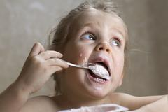 A young girl making a mess out of eating yogurt Stock Photos