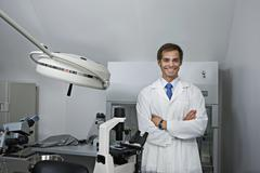 A cheerful research technician standing in a research lab, arms crossed - stock photo
