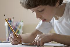 A boy drawing with a pencil - stock photo