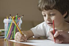 A boy and a friend drawing with colored pencils, viewpoint of boy - stock photo