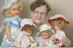 A senior woman with her collection of old-fashioned dolls Stock Photos