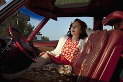 Pretty rockabilly nainen istuu etupenkillä vanhojen autojen Kuvituskuvat