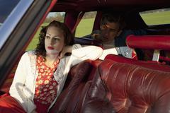 Rockabilly nainen ja mies istuu vanhojen autojen Kuvituskuvat