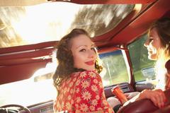 Kaksi rockabilly naiset hauskaa etupenkillä vanhojen autojen Kuvituskuvat