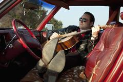 A rockabilly guy playing an acoustic guitar while sitting in his vintage car Stock Photos