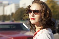 A pretty rockabilly woman standing near a vintage care, focus on woman Kuvituskuvat