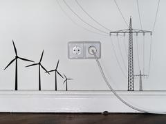 A plug in an outlet in between decals of wind turbines and electricity pylons Stock Photos