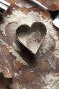 Heart shaped pastry cutter on floury table Stock Photos