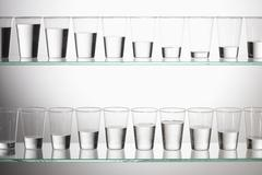 Two shelves with glasses of water filled with varying amounts of water - stock photo