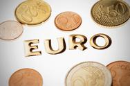 Stock Photo of Single word 'money' in gold lettering surrounded by euro coins