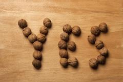 Single word 'yes' spelled with walnuts - stock photo