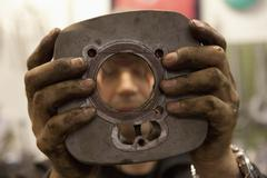 Mechanic showing motorcycle cylinder Stock Photos