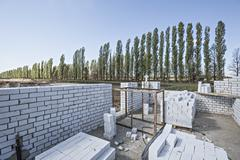 Wall and bricks at construction site with diminishing trees in the background Stock Photos