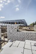 Incomplete brick wall with construction frame in background of construction site Stock Photos