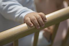 Baby's hand on crib railing Stock Photos