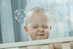 Baby squeezing eyes shut as bubbles pass his head Stock Photos