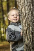 A young boy standing by a tee trunk and smiling happily Stock Photos