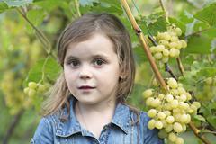 A young girl standing next to a grape vine Stock Photos