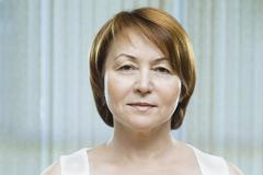 A mature woman looking serenely into the camera Stock Photos
