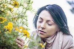 A young woman considering a yellow wildflower Stock Photos