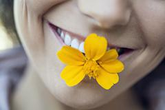 A young grinning woman holding a single flower in her mouth Stock Photos