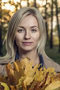 A young woman holding a bunch of autumn leaves in nature Stock Photos