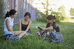 Two friends in a park listening to their friend read from a book Stock Photos