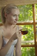 A beautiful woman in a nightie sitting by a window drinking tea Stock Photos