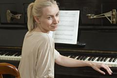 A beautiful woman sitting at a piano Stock Photos