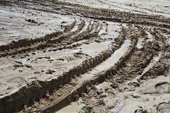 Deep tire tracks imprinted on a muddy terrain Stock Photos