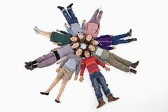 A group of kids lying on their backs in a circle Stock Photos