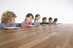 Six sad kids looking down longingly at their empty plates - stock photo
