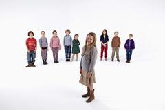 Stock Photo of A girl standing in front of a line of kids