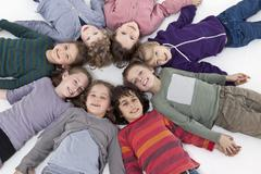 A group of kids lying on their backs in a circle, heads touching Stock Photos