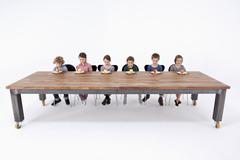 Six kids looking down at apples on their plates with uncertainty - stock photo