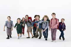 A group of school kids wearing backpacks and running forward Stock Photos