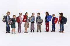 A row of school children wearing backpacks and standing in a row - stock photo