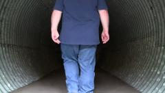 OVERWEIGHT MAN WALKING INTO CORRUGATED CULVERT UNDERPASS - stock footage