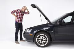 A man standing next to a broke down car, looking down at engine in frustration Stock Photos