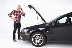 A man standing next to a broke down car while using a cell phone Stock Photos