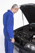 An auto mechanic looking under the hood of a car thoughtfully - stock photo