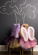 Two girls dressed as angels in front of blackboard with image of tree Stock Photos