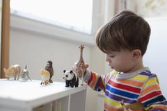 A little boy playing with some toy animal figurines on the floor of his bedroom Stock Photos