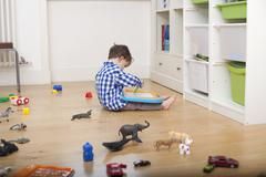 A boy sitting on the floor, drawing on a tablet, surrounded by various toys - stock photo