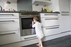 A toddler leaning on an oven door, peeking inside Stock Photos