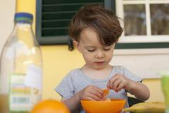 Stock Photo of A boy preparing to eat a slice of fresh orange for breakfast