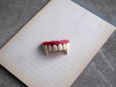 A set of vampire fangs on top of a note pad of lined paper Stock Photos