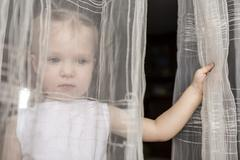 Girl looking out between curtains of open window - stock photo