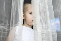 Girl peeking between translucent curtains Stock Photos